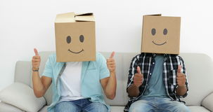 Silly employees with boxes on their heads giving thumbs up. In creative office stock footage
