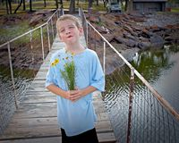 Silly face. A boy with a bouquet of flowers doing a silly face Royalty Free Stock Image