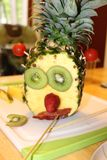 Silly Face Pineapple Fruit Art. Pineapple fruit art made to look like silly face. Kiwis, strawberries, and bacon royalty free stock photography