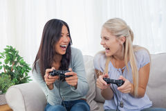 Silly friends playing video games and laughing. At home on the couch Stock Photography