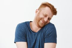 Silly and funny caucasian redhead guy with bristle, tilting head and leaning on shoulder with lovely and cute expression royalty free stock image