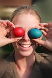 Silly girl. S holding in front of his eyes easter eggs Stock Photo
