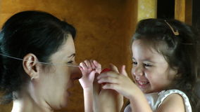 Silly girl puts clown nose on mother
