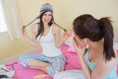 Silly girl trying on a wool hat for her laughing friend Royalty Free Stock Photo