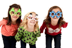 Silly girls wearing fun christmas glasses Royalty Free Stock Image