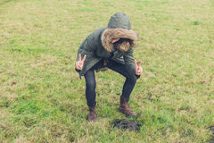 Silly hipster posing with poo. A silly young hipster person is in a field and is posing with some magnificent looking cow dung Royalty Free Stock Images