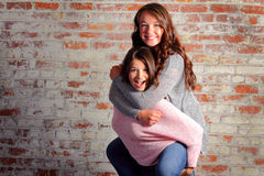 Silly Horse Play. Two pretty brunette teenage girls horsing around playing piggyback in front of a brick wall. Copy Space Stock Photography