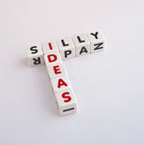 Silly ideas. Text ' silly ' and ' ideas ' with letters inscribed in uppercase and arranged crossword style with common letter ' i '  on bright background Royalty Free Stock Photography