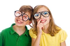 Silly Kids. A young boy and girl with funny glasses on.  They each have cheesy grins and the girl is picking her nose Royalty Free Stock Photo