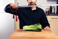 Silly man cutting lettuce with sword Royalty Free Stock Images