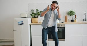 Man in headphones singing in spoon in kitchen dancing playing imaginary guitar stock footage