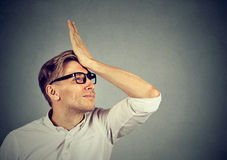 Silly man slapping hand on head having duh moment Stock Photography