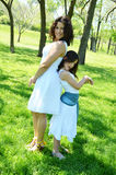Silly Mother and Daughter. Mother and daughter standing back to back and being silly Royalty Free Stock Image