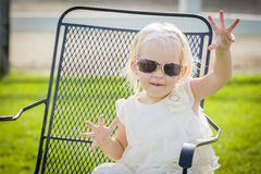 Silly Playful Toddler Girl Wearing Sunglasses Outside at Park Stock Photo