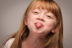 Silly Portrait of an Adorable Red Haired Girl on Grey Stock Image