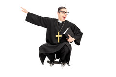 Silly priest riding a small skateboard Stock Images