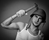 Silly repairman in helmet with hammer Stock Photo