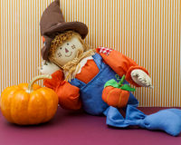 Silly Scarecrow Leaning Against Pumpkin Stock Photography