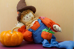 Silly Scarecrow Leaning Against Pumpkin Stock Image
