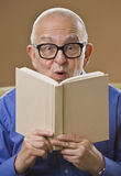 Silly senior man reading book. Silly senior man with glasses reading book, looking at the camera. Vertical Royalty Free Stock Images