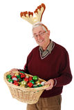 Silly Senior Reindeer. A silly senior man holding a basket of colorful Christmas bulbs while wearing reindeer antlers.  On a white background Stock Photo