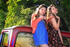 Silly Teen BFF Girls. Two happy teen girls with long brown hair, hanging out laughing together in the back of a pickup. Shallow depth of field. Copy space Royalty Free Stock Photo