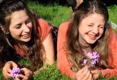 Silly Teen BFF Girls. Two happy teen girls with long brown hair, lounging in the grass hanging out laughing together. Shallow depth of field Stock Image