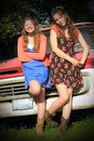Silly Teen BFF Girls. Two silly pretty teenaged girls with long brown hair, hanging out laughing together in front of an old pickup. Shallow depth of field Stock Image
