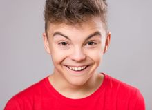 Teen boy portrait. Silly teen boy making grimace - funny face. Child on gray background. Emotional portrait of caucasian teenager looking at camera Royalty Free Stock Photo