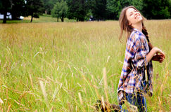 Silly Teen Girl. A pretty silly teenage girl with long brown braided hair recreating in a field of tall grass wearing a blue plaid shirt. Shallow depth of field Stock Image