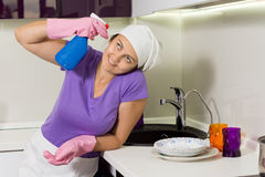 Silly woman holding spray cleaner to her head Royalty Free Stock Photography