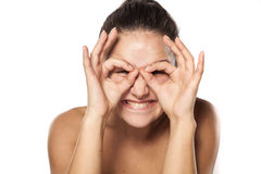 Silly woman without makeup. Silly young woman making glasses with her fingers Stock Photos