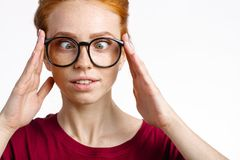 Silly woman smiling face and squinting eyes and touching glasses. Silly redhead freckles woman smiling face and squinting eyes and touching glasses Stock Photo