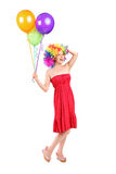 Silly woman with wig holding balloons Stock Photos
