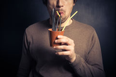 Silly young man drinking from leather cup with straws Stock Image