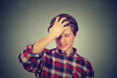 Silly young man, slapping hand on head having a duh moment Stock Photos