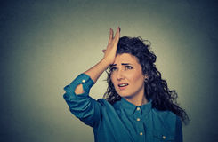 Silly young woman, slapping hand on head having duh moment Royalty Free Stock Photography