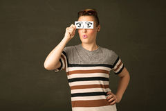 Silly youngster looking with hand drawn eye paper Stock Photography
