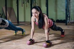 Silna dysponowana kobieta podnosi z dumbbells podczas treningu w gym robić pcha obrazy royalty free