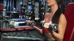 Silna dziewczyna zealously pompuje mięśnie jej ręki zbiory wideo