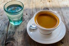 Silna i ciemna kawa w białej porcelany filiżance słuzyć z szkłem woda na stronie na drewnianym stole outdoors Obrazy Stock