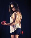 Silna młoda kobieta robi bicep kędziorom Zdjęcia Stock