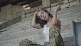 Silna młoda kobieta w wojskowego uniformu obsiadaniu na zimnych betonowych schodkach w zaniechanym budynku dziewczyna 2th lat con zbiory wideo