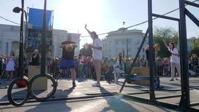 Silna samiec z sztucznym cieki podwyżek kettlebell obok kobieta sędziego na sport rywalizacjach w słonecznym dniu i zbiory wideo