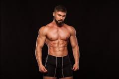 Silna Sportowa mężczyzna sprawności fizycznej modela półpostać pokazuje sześć paczek abs Odizolowywający na Czarnym tle z Copyspa Obraz Royalty Free