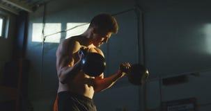 Silnego caucasian mężczyzna podnośni kettlebells w gym zdjęcie wideo