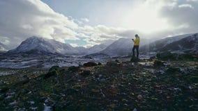 Silnego mężczyzna wycieczkowicz bierze fotografię z mądrze telefonem przy halnym szczytem Fenomenalny brzask zbiory