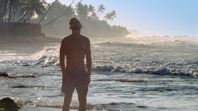 Silnego mężczyzny rozciągliwość głowa i szyja na plażowym zwolnionym tempie zbiory