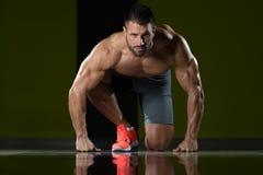 Silni Mięśniowi mężczyzna Klęczy Na podłoga Zdjęcie Stock