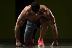 Silni Mięśniowi mężczyzna Klęczy Na podłoga Fotografia Stock